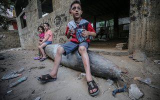 Παιδιά στην Πόλη της Γάζας κάθονται σε πύραυλο που έριξαν τα ισραηλινά μαχητικά αλλά δεν εξερράγη. (Φωτ. EPA / MOHAMMED SABER)