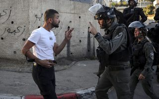 Φωτ. AP/Mahmoud Illean: Παλαιστίνιος διαδηλωτής και Ισραηλινός αστυνομικός διαπληκτίζονται στη συνοικία των εποικισμών Sheikh Jarrah, 15 Μαΐου 2021