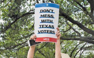 «Μην τα βάζετε με τους ψηφοφόρους του Τέξας» προτάσσει διαδηλώτρια υπέρ της καθολικής ψήφου. Σε εθνικό επίπεδο, το Ρεπουμπλικανικό Κόμμα προσπαθεί να θέσει όλο και περισσότερα εμπόδια στο δικαίωμα του εκλέγειν (φωτ. REUTERS).