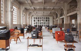 Κουτλού Αταμάν, «Küba», 2004. Εγκατάσταση βίντεο 40 καναλιών με ήχο, 40 χρησιμοποιημένες καρέκλες, 40 τραπέζια, 40 τηλεοράσεις. Στο βάθος, το έργο του Ανταμ Πέντλετον «Our Ideas #2», 2018.
