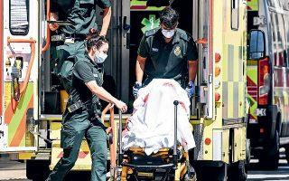 Aσθενής με COVID-19 κατά τη μεταφορά του σε νοσοκομείο του Λονδίνου. Αρση των περιοριστικών μέτρων ανέμεναν οι Βρετανοί πολίτες, lockdown τεσσάρων εβδομάδων εισέπραξαν (φωτ. EPA).