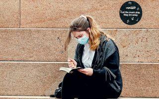Nεαρή γυναίκα διαβάζει φορώντας προστατευτική μάσκα, σε εξωτερικό χώρο, στο Λίβερπουλ. Χαρακτηριστικό της νέας μετάλλαξης του ιού είναι η υψηλή μεταδοτικότητα, κατά 50%-70% μεγαλύτερη από το βρετανικό στέλεχος. (Φωτ. REUTERS)