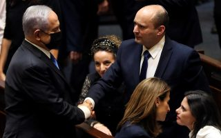 Με μία τυπική χειραψία ο Μπενιαμίν Νετανιάχου (αριστερά) συνεχάρη τον πρώην προσωπάρχη του Ναφτάλι Μπένετ που ανέλαβε πρωθυπουργός (φωτ.: Reuters).