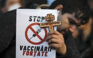 Αρνητές του κορωνοϊού και πολέμιοι των εμβολίων βγαίνουν συχνά στους δρόμους του Βουκουρεστίου/Φωτ. AP:Vadim Ghirda