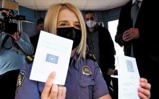 Αστυνομικός ελέγχει το ευρωπαϊκό πιστοποιητικό COVID ταξιδιώτη, στα σύνορα της Κροατίας με τη Σλοβενία. (Φωτ. )