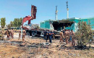 Aνδρες των ιρακινών στρατιωτικών δυνάμεων επιθεωρούν το σημείο ρίψης ρουκετών, στην αεροπορική βάση του Ανμπαρ (φωτ. REUTERS).
