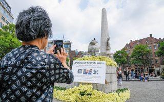 Γυναίκα φωτογραφίζει το σημείο όπου έστησαν την ενέδρα κατά του Ντε Βρις, στο Αμστερνταμ, στολισμένο με 4.000 τριαντάφυλλα και φωτογραφίες του, μαζί με τη φράση «Επίθεση στην ελευθερία του Τύπου». (Φωτ. A.P.)