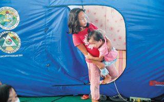 Παιδιά σε γυμναστήριο που έχει μετατραπεί προσωρινά σε καταφύγιο, εξαιτίας της πλημμύρας που προκάλεσαν οι έντονες βροχοπτώσεις, χθες, στην πόλη Μαρικίνα, στις Φιλιππίνες.