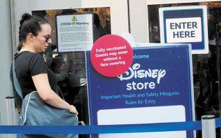 Οι πλήρως εμβολιασμένοι μπορούν να εισέρχονται χωρίς προστατευτική μάσκα, ενημερώνει τους πελάτες της η Disney στην είσοδο καταστήματος με είδη της εταιρείας, στη Νέα Υόρκη. (Φωτ. REUTERS)