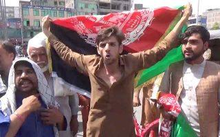 Πολίτες με αφγανικές σημαίες διαδηλώνουν κατά της κατάληψης της εξουσίας από τους Ταλιμπάν στην πόλη Τζαλαλαμπάντ. (Φωτ. Pajhwok Afghan News/Handout via REUTERS)