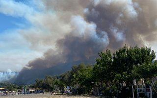 Πυκνοί καπνοί σκεπάζουν τον ουρανό πάνω από το χωριό Βασιλικά (όπως φαίνεται από την παραλία Ψαροπούλι).