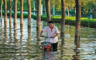 Πλημμυρισμένος δρόμος σε επαρχία της Κίνας. Η κλιματική αλλαγή δεν είναι σαν την πανδημία. Δεν αναχαιτίζεται με εμβόλια. Χρειάζεται αλλαγή φιλοσοφίας, δραστικά μέτρα, αποφάσεις εδώ και τώρα. (Φωτ. A.P. / Dake Kang)