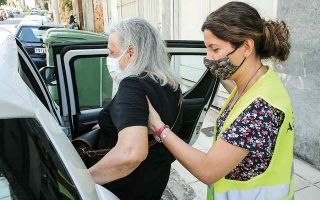 Η νοσηλεύτρια Βασιλική Τιακούδη βοηθάει τη Μαργαρίτα Δημητριάδου να μπει στο όχημα του «Βοήθεια στο Σπίτι», πριν τη συνοδεύσει στο νοσοκομείο. (Φωτ. ΝΙΚΟΣ ΚΟΚΚΑΛΙΑΣ)