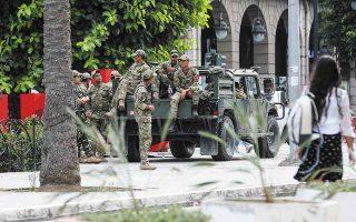 Στρατιώτες σε κεντρικό δρόμο της Τύνιδας. Στη χώρα απαγορεύθηκαν οι συναθροίσεις άνω των τριών ατόμων και επεβλήθη απαγόρευση κυκλοφορίας από τις επτά το απόγευμα. (Φωτ. EPA / STRINGER)
