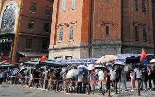 Οι κάτοικοι της Γουχάν στοιχίζονται μπροστά από τον Πύργο νερού για να υποβληθούν σε τεστ κορωνοϊού (φωτ. China Daily via REUTERS).
