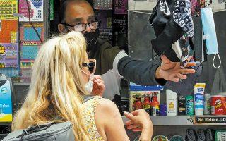 Μια Νεοϋορκέζα αγοράζει μάσκα. Οι περισσότεροι Αμερικανοί έχουν μπερδευτεί από τις αντιφατικές συστάσεις για τη χρήση της (φωτ. AP Photo / Mary Altaffe).