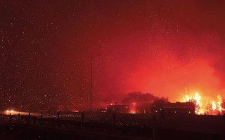 Εως αργά το βράδυ η Πυροσβεστική έδινε μάχη για να περιορίσει τη φωτιά, η οποία σε διάφορα σημεία περνούσε την εθνική οδό (φωτ. A.P. Photo / Michael Varaklas).