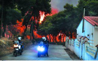 Αστυνομικοί, στο συγκεκριμένο στιγμιότυπο στη Βαρυμπόμπη, γυρίζουν δρόμο δρόμο, σπίτι σπίτι και ζητούν από τους κατοίκους να απομακρυνθούν. Σε κάποιες περιπτώσεις δίνουν «μάχη» για να τους πείσουν. Φωτ. INTIME NEWS / ΔΗΜΗΤΡΗΣ ΜΠΙΡΝΤΑΧΑΣ