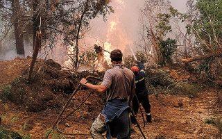 Πυροσβέστες και κάτοικοι προσπαθούν να ελέγξουν την πυρκαγιά έξω από το χωριό Γαλατσώνα στην Εύβοια (φωτ. SOOC).