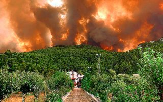 Ενα σπίτι το οποίο η πυροσβεστική ομάδα του κ. Γερόλυμπου έσωσε από τις φλόγες, στις Αφίδνες, στέκει αγέρωχο, ενώ ο ουρανός έχει καλυφθεί εξ ολοκλήρου από τον καπνό.
