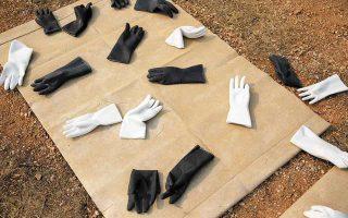 Ακουμπισμένα σε δύο μαρμάρινα πανιά τα δίχρωμα γάντια, που μοιάζουν με τα συνθετικά που χρησιμοποιούμε στις εργασίες, αποτελούν μια πρόκληση για τον γλύπτη να αποδείξει τη δεξιότητά του.