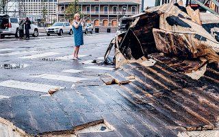 Γυναίκα φωτογραφίζει την ξεριζωμένη στέγη ενός κτιρίου, σε δρόμο της Γαλλικής Συνοικίας της Νέας Ορλεάνης, μετά το πέρασμα του τυφώνα «Αϊντα» (φωτ. EPA).