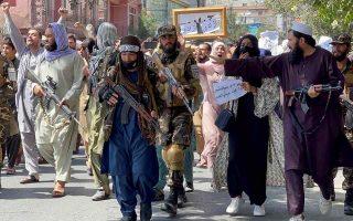Ένοπλοι Ταλιμπάν προπορεύονται των διαδηλωτών κατά τη διάρκεια κινητοποίησης στην Καμπούλ. (Φωτ. REUTERS/Stringer)