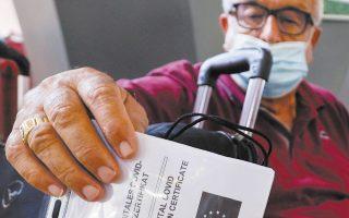 Ιταλός πολίτης επιδεικνύει το πιστοποιητικό εμβολιασμού του για COVID-19 στον κεντρικό σιδηροδρομικό σταθμό της Νάπολης (φωτ. REUTERS).