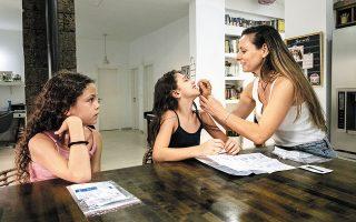 Μια μητέρα παίρνει δείγμα από τη δεκάχρονη κόρη της, Αριελ, για να της κάνει τεστ κορωνοϊού ενόψει της πρώτης ημέρας λειτουργίας των σχολείων στο Ισραήλ. Η εκτόξευση των κρουσμάτων στη χώρα, λόγω της μετάλλαξης «Δέλτα», προκαλεί ανησυχία για το μέλλον της σχολικής χρονιάς (φωτ. A.P. Photo / Tsafrir Abayov).