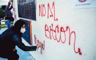 Νεαροί πολίτες του Ελ Σαλβαδόρ γράφουν με σπρέι συνθήματα κατά της πολιτικής των συναλλαγών με bitcoin (φωτ. EPA).