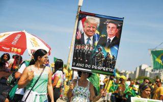 Υποστηρικτές του προέδρου της Βραζιλίας, Ζαΐρ Μπολσονάρο, διαδήλωσαν χθες μαζικά, με συνθήματα εναντίον του Ανωτάτου Δικαστηρίου και του Κογκρέσου της χώρας. Οι ανησυχίες για προετοιμασία αντιδημοκρατικής εκτροπής τροφοδοτούνται από πλακάτ, όπως το εικονιζόμενο, που γράφει «χρονιά ξυπνήματος» κάτω από τη φωτογραφία οπλισμένων στρατιωτών.(φωτ. REUTERS / Pilar Olivares).