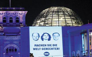 «Κάνετε τον κόσμο πιο δίκαιο» προτείνουν Γερμανοί ακτιβιστές, συνοδεύοντας το μήνυμά τους με φωτογραφίες των υποψηφίων για την καγκελαρία, Ολαφ Σολτς, Αναλένα Μπέρμποκ και Αρμιν Λάσετ, στο Βερολίνο (φωτ. REUTERS).