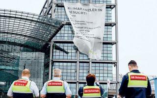 Μέλη της Greenpeace ανήρτησαν στη νότια πρόσοψη του σιδηροδρομικού σταθμού του Βερολίνου γιγαντιαίο πανό διαστάσεων 16χ22 μέτρων, που κωδικοποιεί τα αιτήματα προς τον/την επόμενο καγκελάριο (φωτ. EPA / FILIP SINGER).