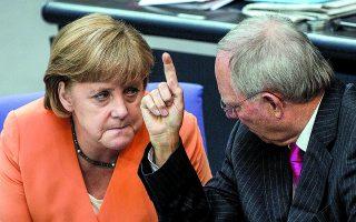 """Μια ανταλλαγή απόψεων με γκριμάτσες από συνεδρίαση του γερμανικού κοινοβουλίου μεταξύ των Μέρκελ και Σόιμπλε τον Ιούλιο του 2012. «Δεν βρισκόταν πάντα """"στο ίδιο μήκος κύματος"""" με τον Σόι-μπλε. Η ίδια δεν το έκρυβε και πολύ """"επιμελώς"""". Κάποιες φορές ο Σόιμπλε, από την πλευρά του, δεν το έκρυβε καθόλου...». Φωτ. A.P. Photoα / Gero Breloer"""