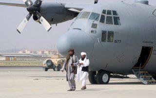 Δύο μέλη των Ταλιμπάν μπροστά σε αμερικανικό πολεμικό αεροσκάφος που είχε παραχωρηθεί στις αφγανικές ένοπλες δυνάμεις (φωτ.: Reuters).