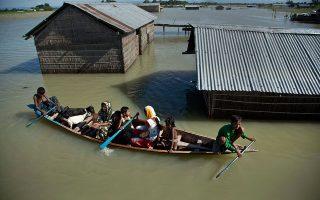 Μέλη οικογένειας πληγέντων από πλημμύρες στην Ινδία, ταξιδεύουν σε μια βάρκα μαζί με τις κατσίκες τους (AP Photo/Anupam Nath)