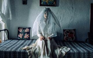 Μια γυναίκα στολίστηκε με νυφικό του 19ου αιώνα στον Παλαιό Παντελεήμονα Πιερίας, καθισμένη στο κρεβάτι της κάμαράς της. (Φωτογραφίες: Μιχάλης Παππάς)