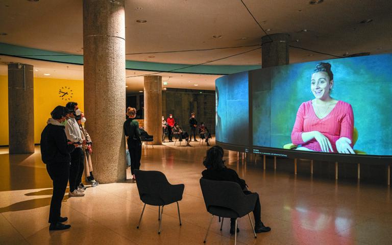 Στο φουαγιέ του Haus der Kulturen der Welt οι επισκέπτες παρακολουθούν τα βίντεο με τις ιστορίες των προσφύγων που συμμετέχουν στο πρότζεκτ. Φωτ. SEBASTIAN BOLESCH